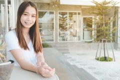 Frau, die auf dem Stuhl betrachtet Kamera und lächelt - Porträt schön sitzt lizenzfreie stockfotos