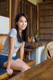 Frau, die auf dem Stuhl in der Kaffeestube sitzt Stockfotografie