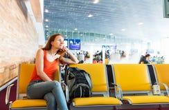 Frau, die auf dem Stuhl in einer Stationshalle sitzt Lizenzfreies Stockfoto