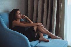 Frau, die auf dem Stuhl sitzt und durch das Fenster schaut Stockfotos