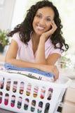 Frau, die auf dem Waschen im Korb sich lehnt Stockfoto
