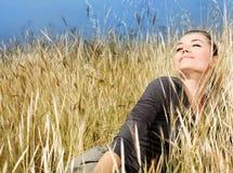 Frau, die auf dem Weizenfeld genießt Stockbild