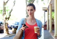 Frau, die auf den Bürgersteig hält Mobiltelefon und Kaffee geht Stockfoto