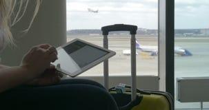 Frau, die auf den Flug mit Tablet-PC wartet stock video footage