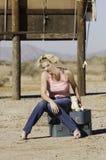 Frau, die auf den Koffern oben schauen sitzt Stockfotografie