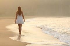 Frau, die auf den Sand des Strandes geht Lizenzfreies Stockfoto