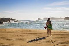 Frau, die auf den Sand eines schönen Strandes geht stockfotos