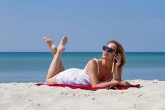 Frau, die auf den Sand nahe dem Meer telefonisch spricht legt Stockfotografie