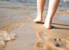 Frau, die auf den Sandstrand lässt Abdruck im Sand geht Setzen Sie Reise auf den Strand lizenzfreies stockfoto