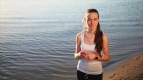 Frau, die auf den Sandstrand plaudert mit ihren Freunden verwenden ihren Smartphone geht stock video