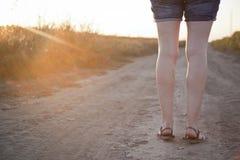 Frau, die auf den Schotterweg geht Stockbild