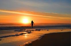 Frau, die auf den Strand bei Sonnenaufgang geht lizenzfreies stockfoto