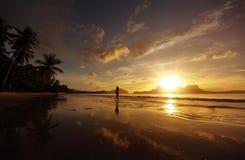 Frau, die auf den Strand gegen die untergehende Sonne über dem isla geht Stockfoto