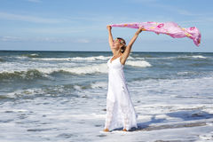Frau, die auf den Strand geht und einen Schal im Wind hält Lizenzfreie Stockbilder