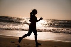 Frau, die auf den Strand läuft Stockfotografie