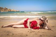 Frau, die auf den Strand legt Lizenzfreies Stockfoto