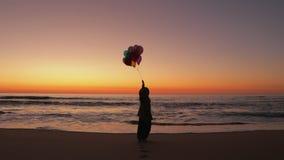 Frau, die auf den Strand mit Ballonen geht stock video