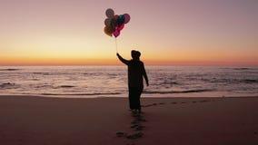 Frau, die auf den Strand mit Ballonen geht stock footage