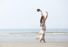 Frau, die auf den Strand mit den angehobenen Armen geht Lizenzfreie Stockfotos