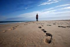 Frau, die auf den Strand schlendert Stockbilder
