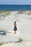 Frau, die auf den Strand schlendert Stockbild