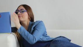 Frau, die auf denkendem Buch der Couch Lese, volles HD sitzt stock footage