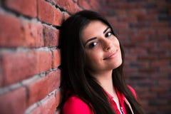 Frau, die auf der Backsteinmauer sich lehnt Lizenzfreie Stockfotografie