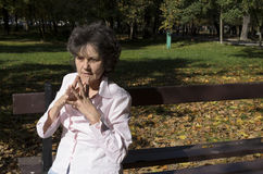 Frau, die auf der Bank im Herbst sich entspannt Stockbild