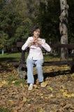 Frau, die auf der Bank im Herbst sich entspannt Stockfotos