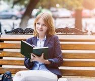 Frau, die auf der Bank mit Tagebuch sitzt Stockbild