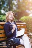 Frau, die auf der Bank mit Tagebuch sitzt Lizenzfreie Stockfotografie