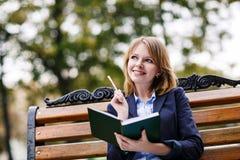 Frau, die auf der Bank mit Tagebuch sitzt Stockfotos