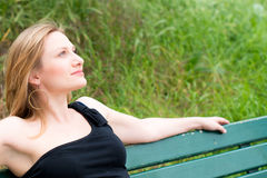 Frau, die auf der Bank sitzt lizenzfreies stockfoto