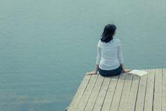 Frau, die auf der Bretttabelle nahe See sitzt Stockbild