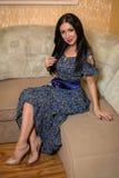 Frau, die auf der Couch im Raum sitzt Stockfotografie