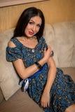 Frau, die auf der Couch im Raum sitzt Lizenzfreie Stockfotos
