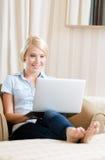 Frau, die auf der Couch mit Computer sitzt Lizenzfreies Stockfoto