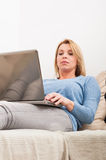 Frau, die auf der Couch mit Laptop auf Schoss sitzt Stockfoto