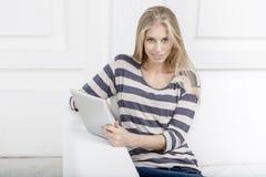 Frau, die auf der Couch mit Tabletten-PC sitzt Stockbilder