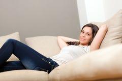 Frau, die auf der Couch sich entspannt Stockfotos