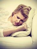 Frau, die auf der Couch sich fühlt sehr unwohl liegt Stockfotos