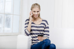 Frau, die auf der Couch sitzt und Kreditkarte hält Stockfotografie