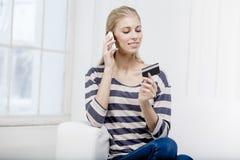Frau, die auf der Couch sitzt und Kreditkarte hält Lizenzfreie Stockfotografie