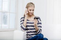 Frau, die auf der Couch sitzt und Kreditkarte hält Lizenzfreie Stockbilder