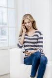 Frau, die auf der Couch sitzt und Kreditkarte hält Lizenzfreies Stockfoto