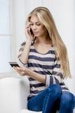 Frau, die auf der Couch sitzt und Kreditkarte hält Stockbild