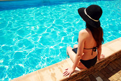Frau, die auf der Leiste des Pools sitzt Stockfotos