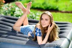 Frau, die auf der Matratze im Garten liegt lizenzfreie stockfotografie