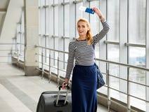 Frau, die auf der Station mit einem Koffer und einem Rucksack spricht und einen Pass in ihren Händen hält erfasst auf einer Reise Stockbild