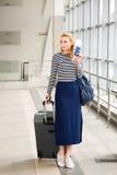 Frau, die auf der Station mit einem Koffer und einem Rucksack spricht und einen Pass in ihren Händen hält erfasst auf einer Reise Stockbilder